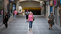A woman walking through Bridgend wearing a face mask