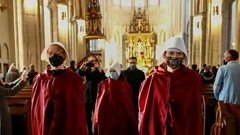 Protesters walk through a cathedral in Lodz, Poland