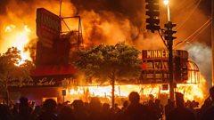A liquor store burns near the Minneapolis police's third precinct