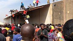 People gather around a warehouse in Bukuru, Nigeria, 24 October 2020