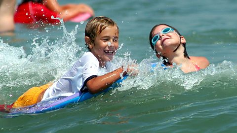 Children play in the surf as they enjoy the cool waters of the Atlantic Ocean