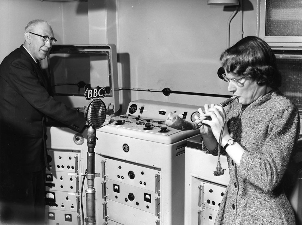 Daphne Oram in 1958 playing an Arabic reed pipe, while Radiophonic Workshop engineer Richard Bird records the sound on a tape machine