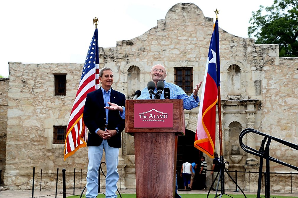 Texas Land Commissioner Jerry Patterson listens as Phil Collins speaks in front of The Alamo, announcing the donation of his collection of artefacts, 2014