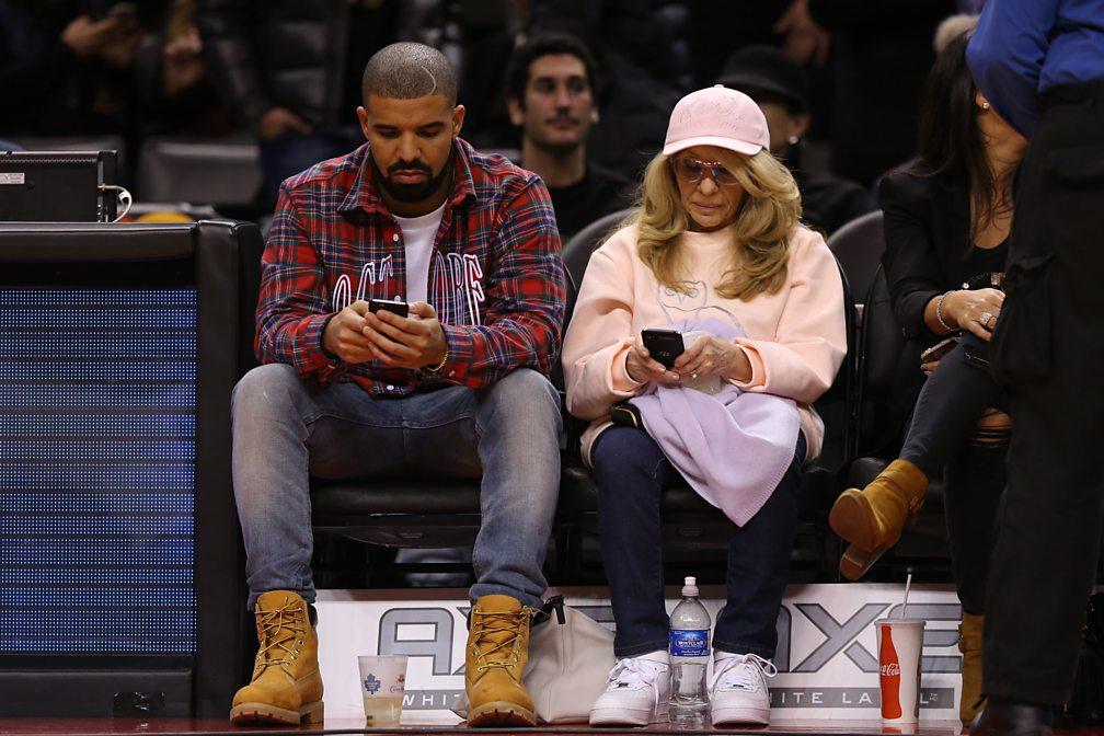 Drake and his mother, Sandi Graham, courtside at a basketball game, 2015