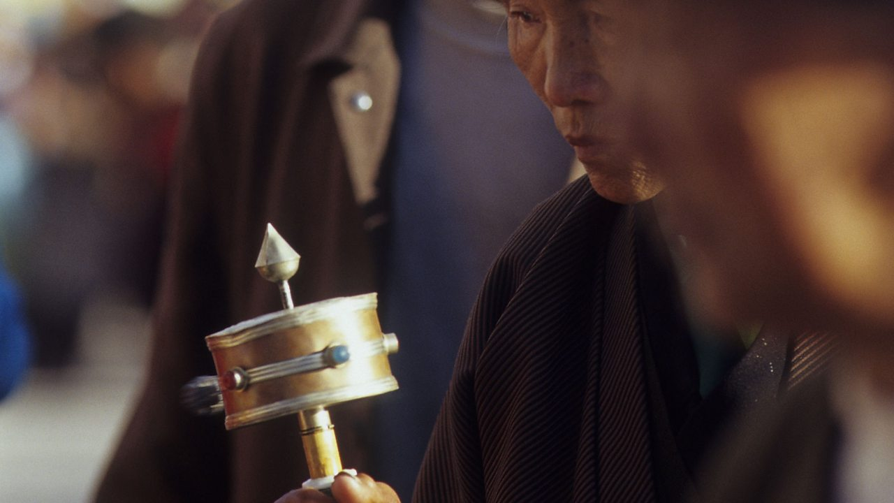 A Tibetan pilgrim in Lhasa using a prayer wheel.