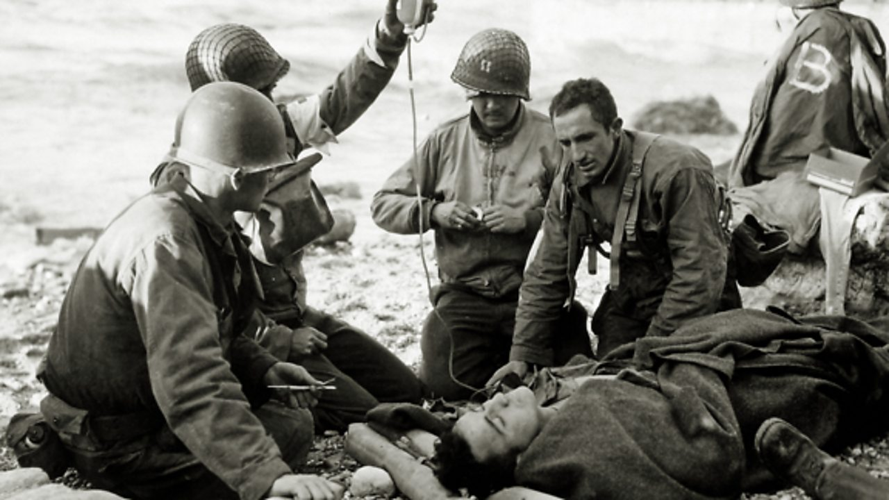 A wounded solider being treated by medics.