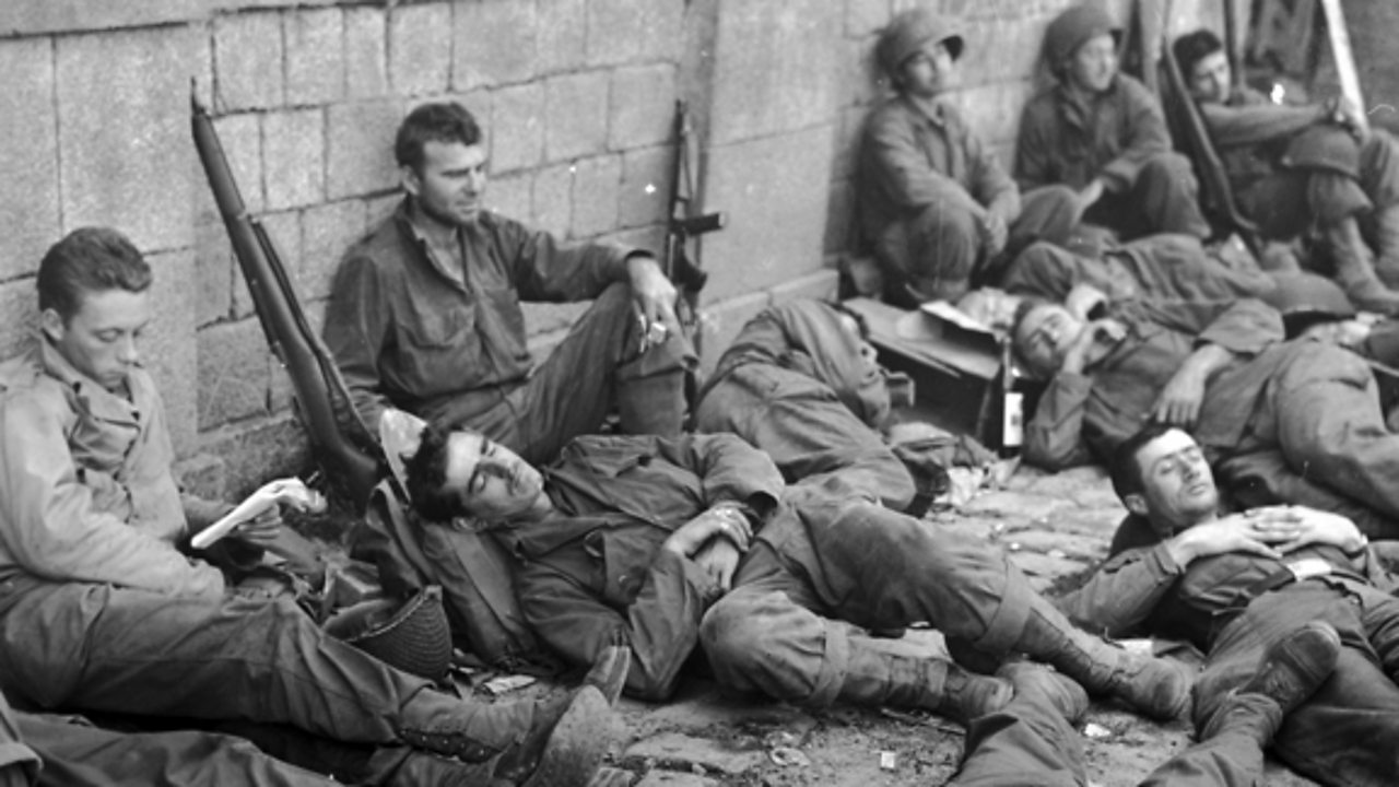 Soldiers leaning against a wall, looking exhausted.