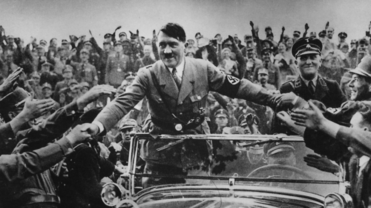 Hitler in a car, being mobbed by supporters.