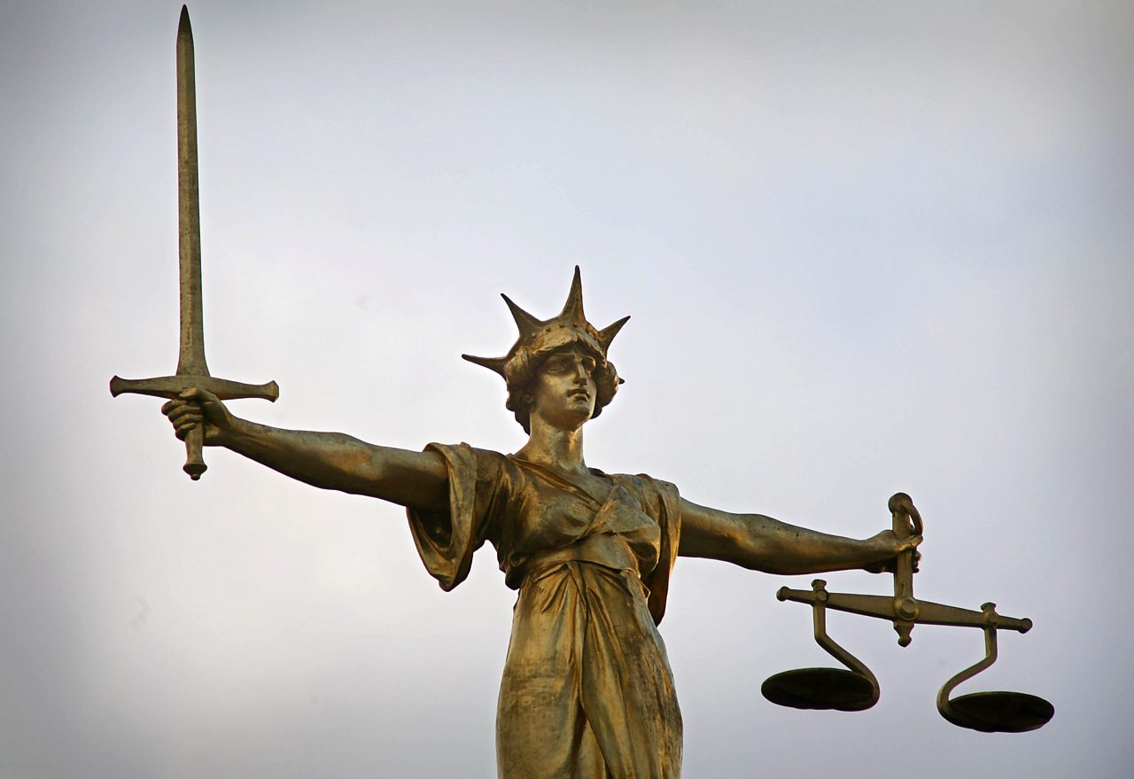 A statue with a figure holding a sword and a set of scales, representing justice.