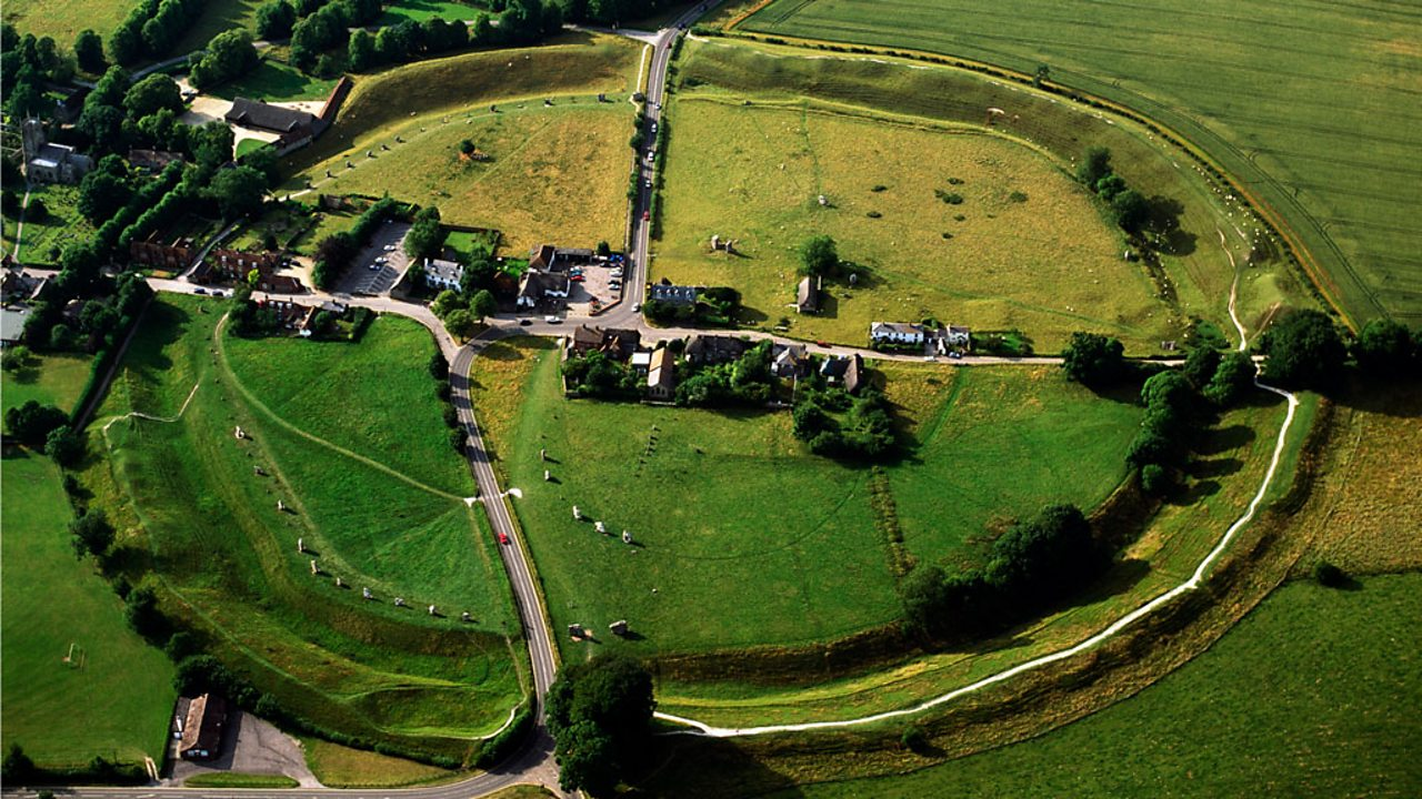 An aerial view of Avebury stone circle, a large stone circle surrounding fields.