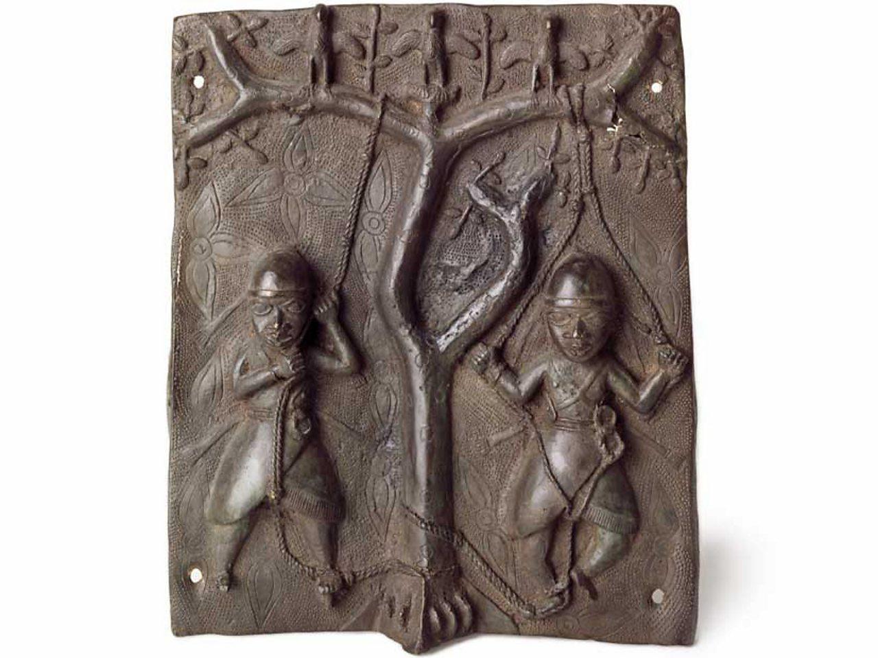 A brass plaque showing acrobats