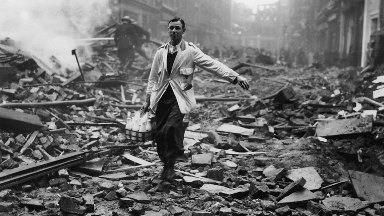 A milkman delivering milk in a London street devastated during a German bombing raid.