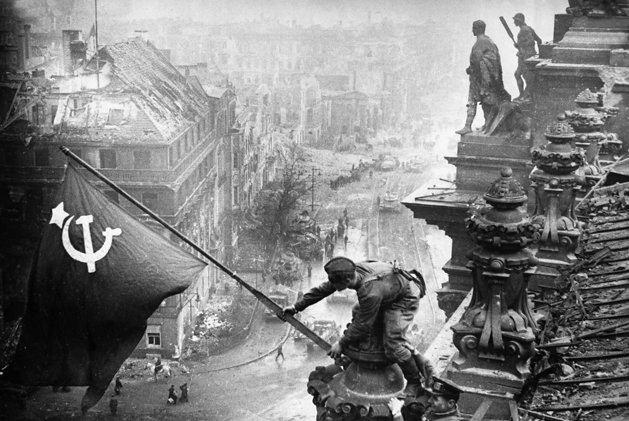 Red Army soldiers raise the Soviet flag over the Reichstag in Berlin on 30 April.