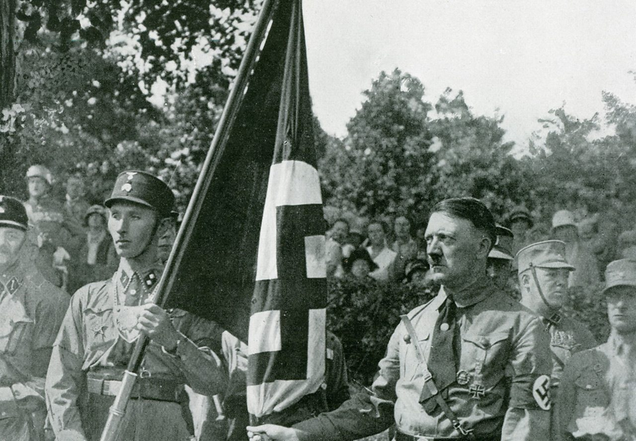 """Hitler poses with the """"blood flag"""" from Beer Hall Putsch."""