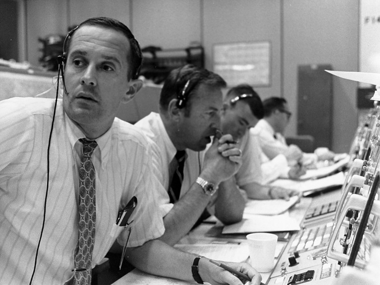 Men at mission control wearing telephone headsets. Left to Right: Charlie Duke; Jim Lovell; Fred Haise.