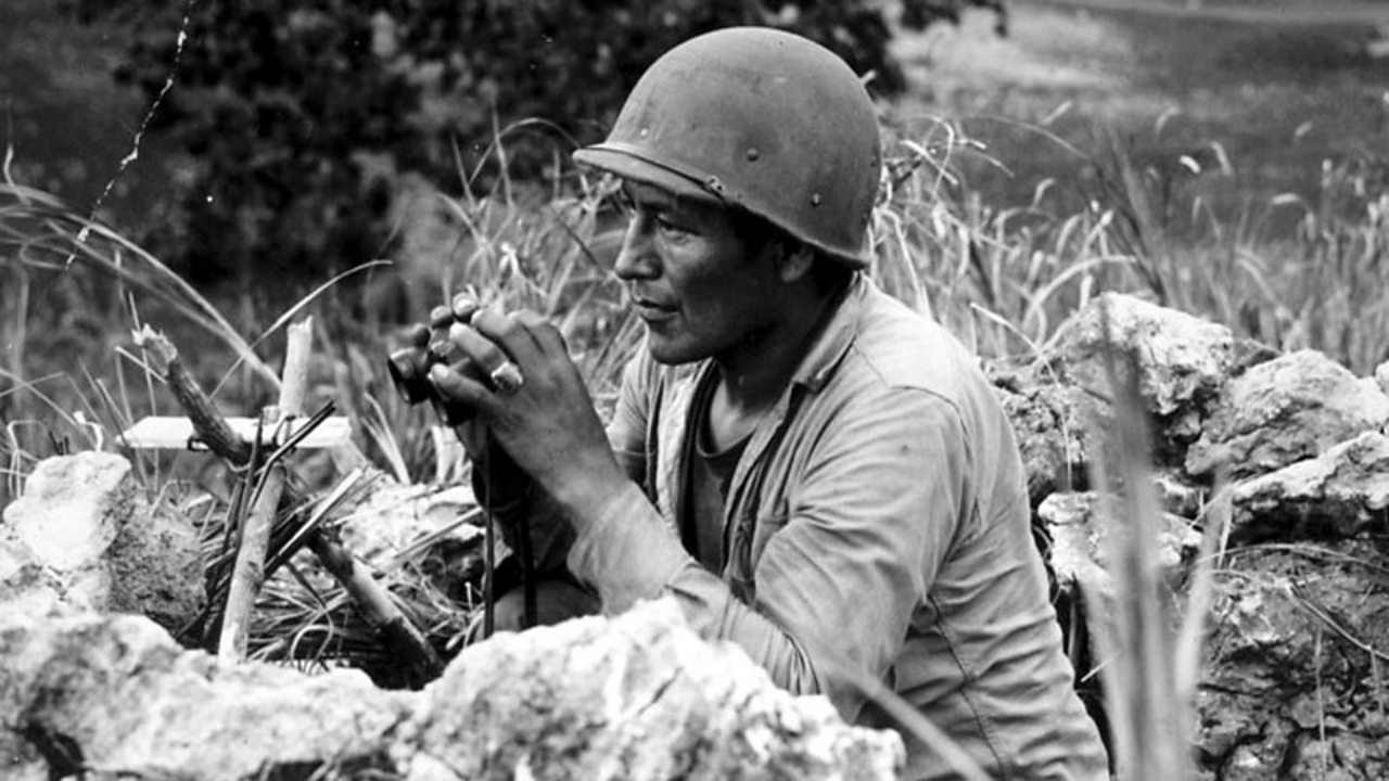 A code talker in a battle, crouching and using binoculars.