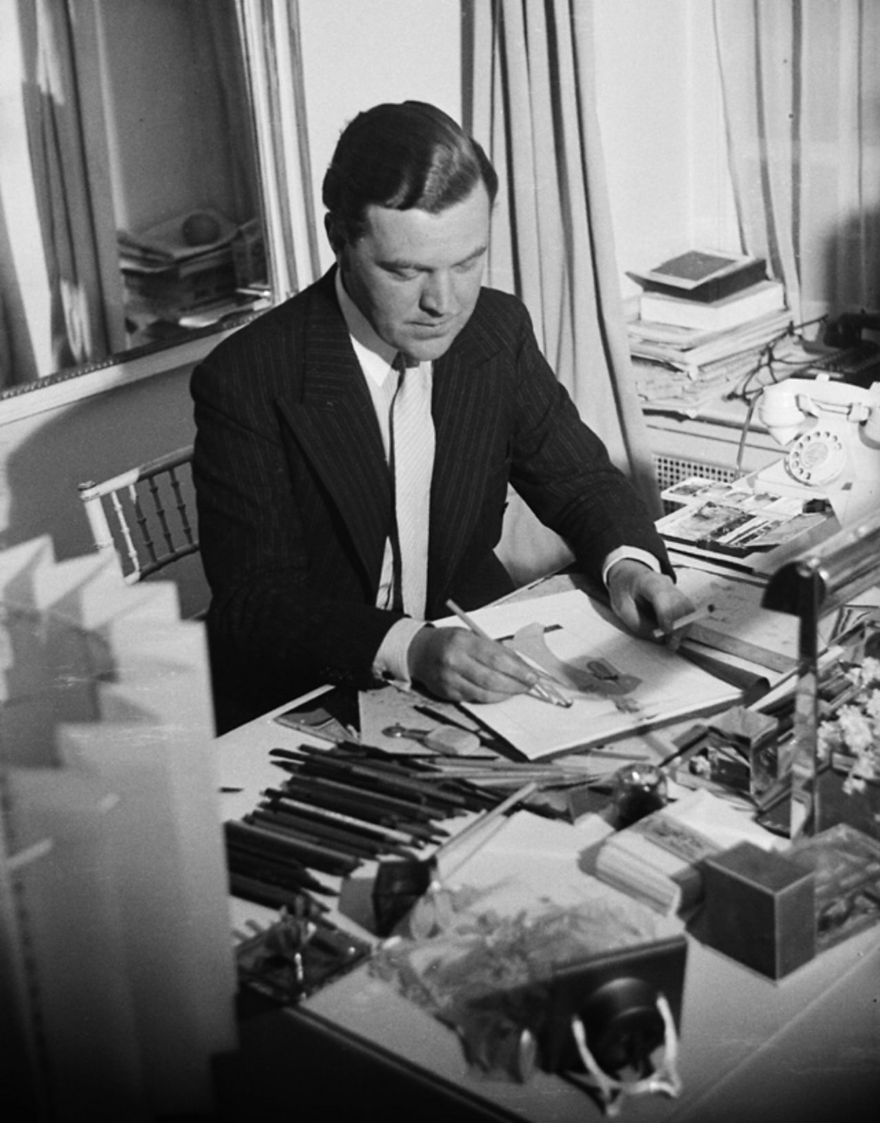 Norman Hartnell, an important designer, designing clothes at his desk.