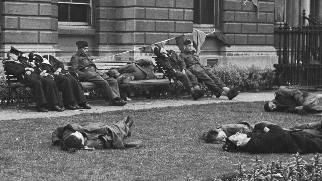 People slumped and lying down after VE day celebrations