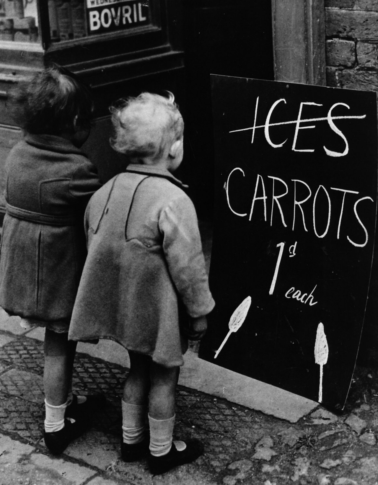Two young children with a board advertising the enticing prospect of carrots on sticks in 1941.