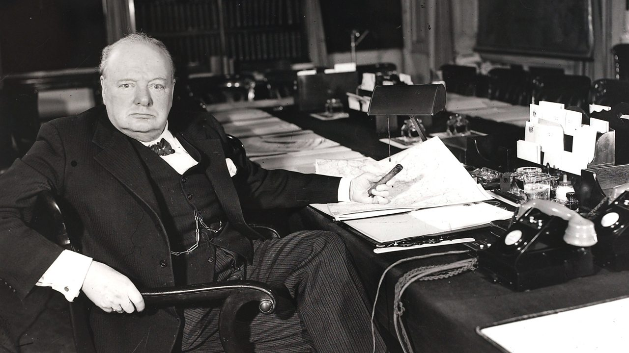 Winston Churchill sitting at a desk with some papers