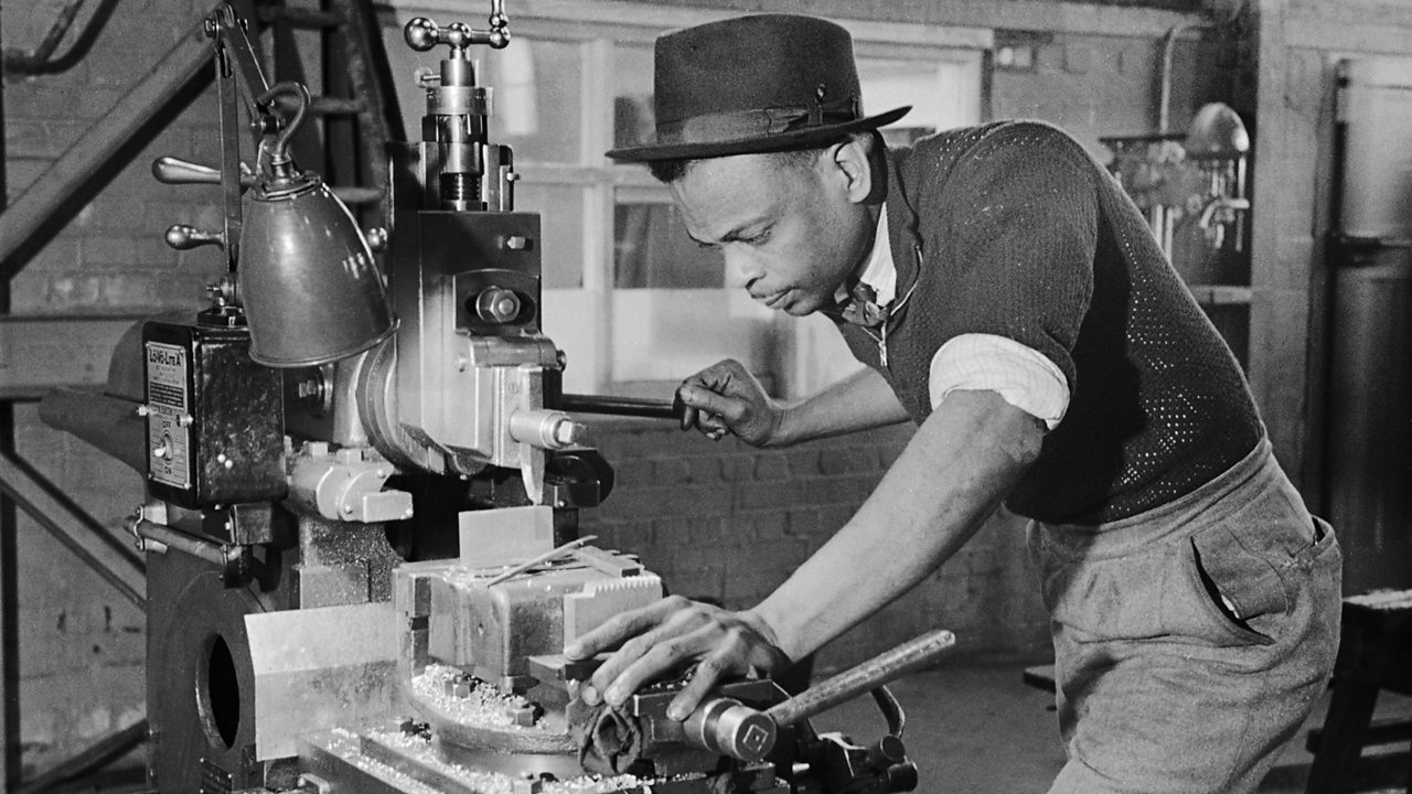A Caribbean man working at a machine in a munitions factory