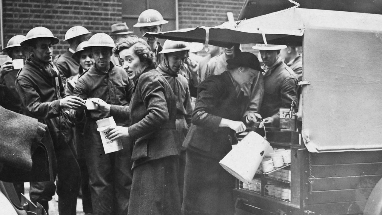 A woman serving soldiers tea from the back of a truck