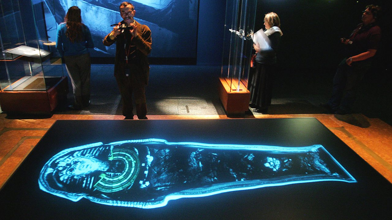 A modern exhibition of Tutankhamun, showing vistors photographing a neon outline of Tutankhamuns coffin.