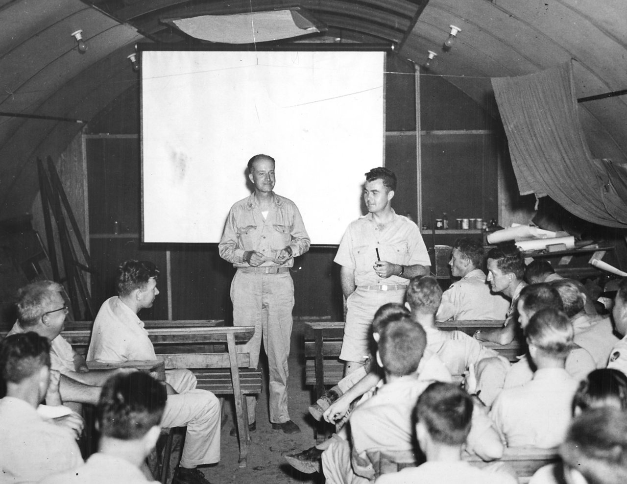 Captain Parsons and Paul Tibbets address their crews ahead of the mission.