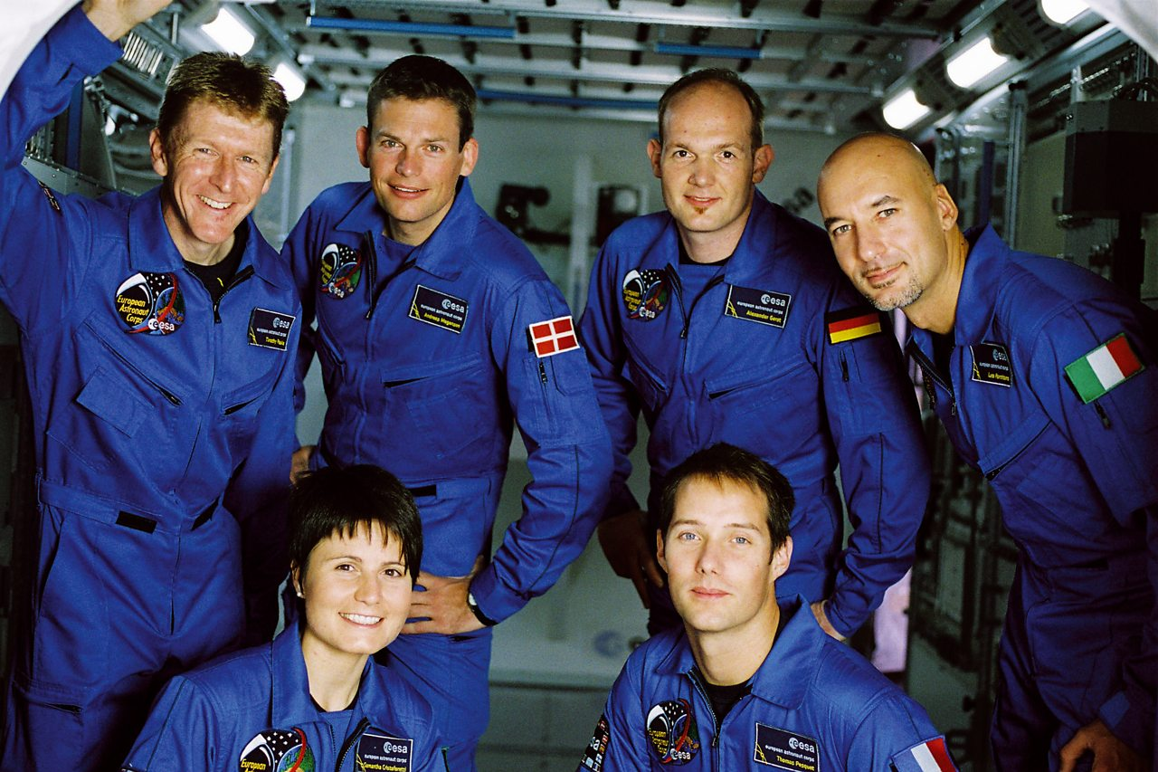 Five newly recruited ESA astronauts standing in blue space suits.