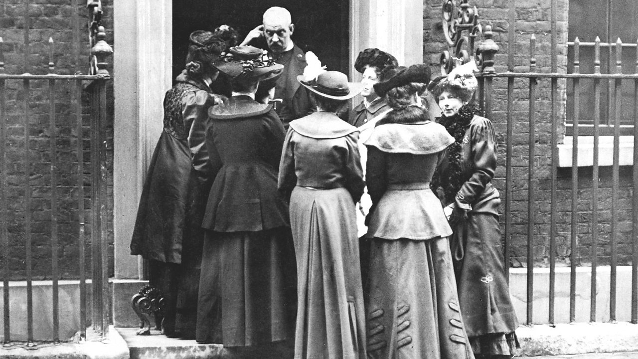 A group of suffragettes gather outside a house.