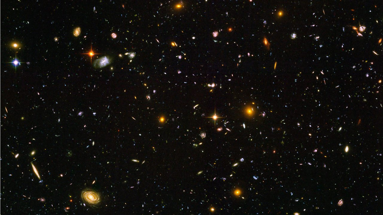 A sea of galaxies floating in space.