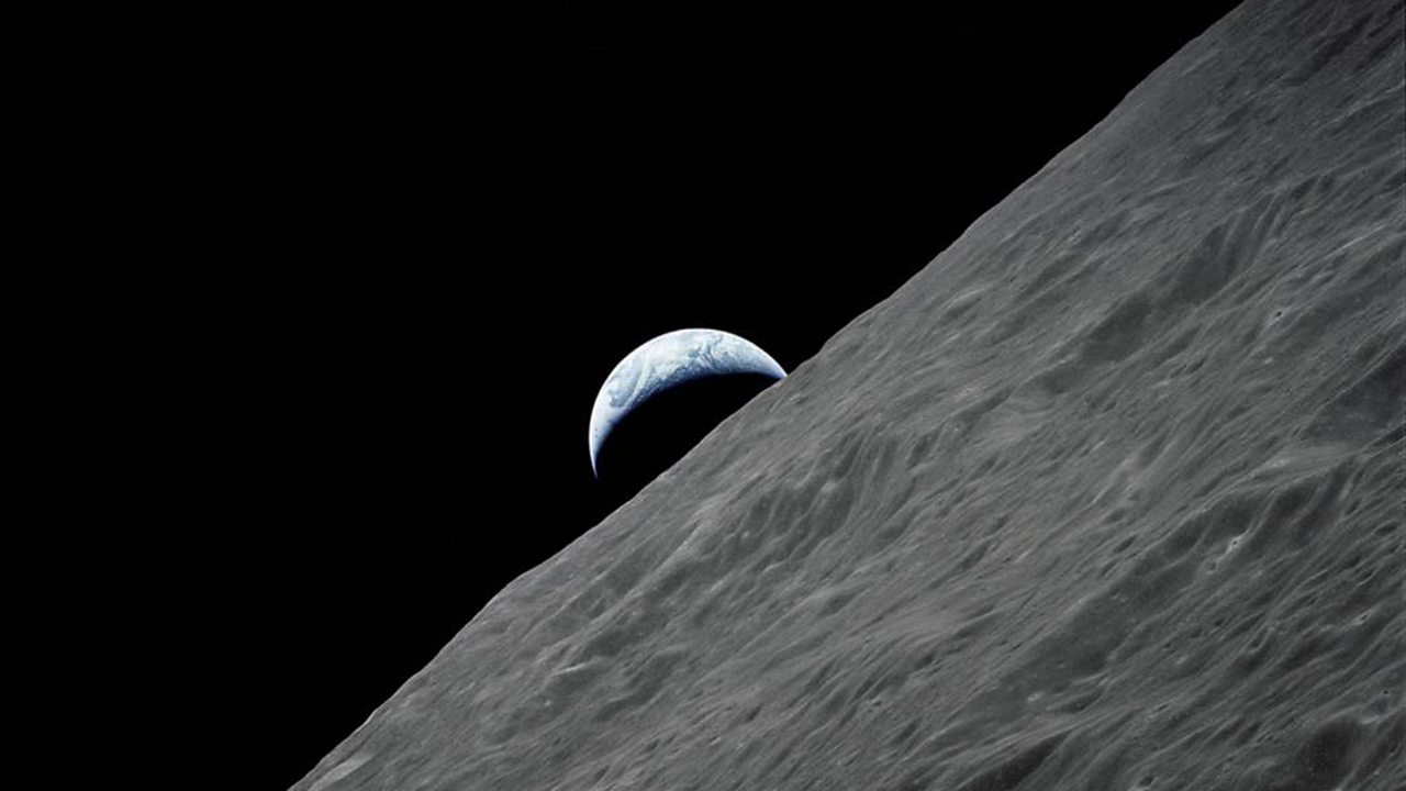 The Earth rising above the surface of the Moon.
