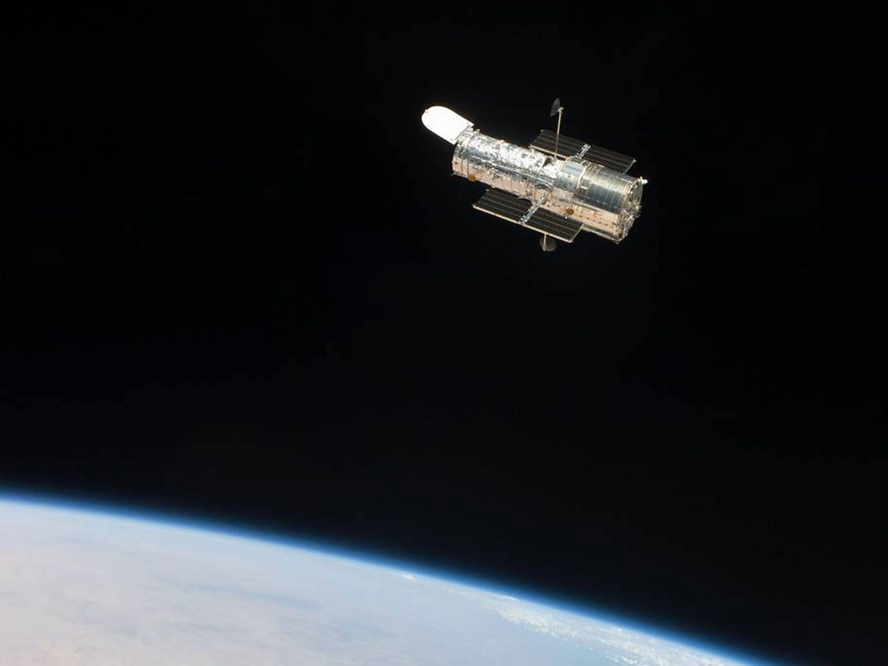 The Hubble Space Telescope floating above the Earth