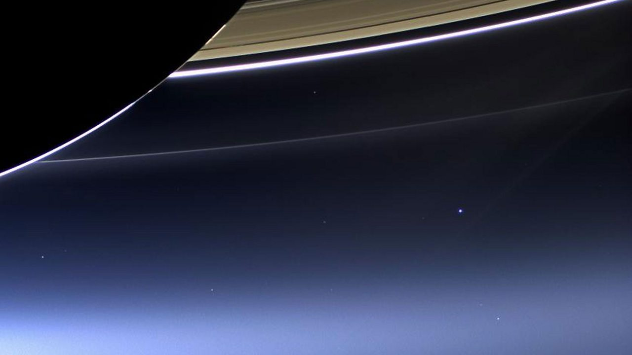 The pale blue dot of Earth below the rings of Saturn.