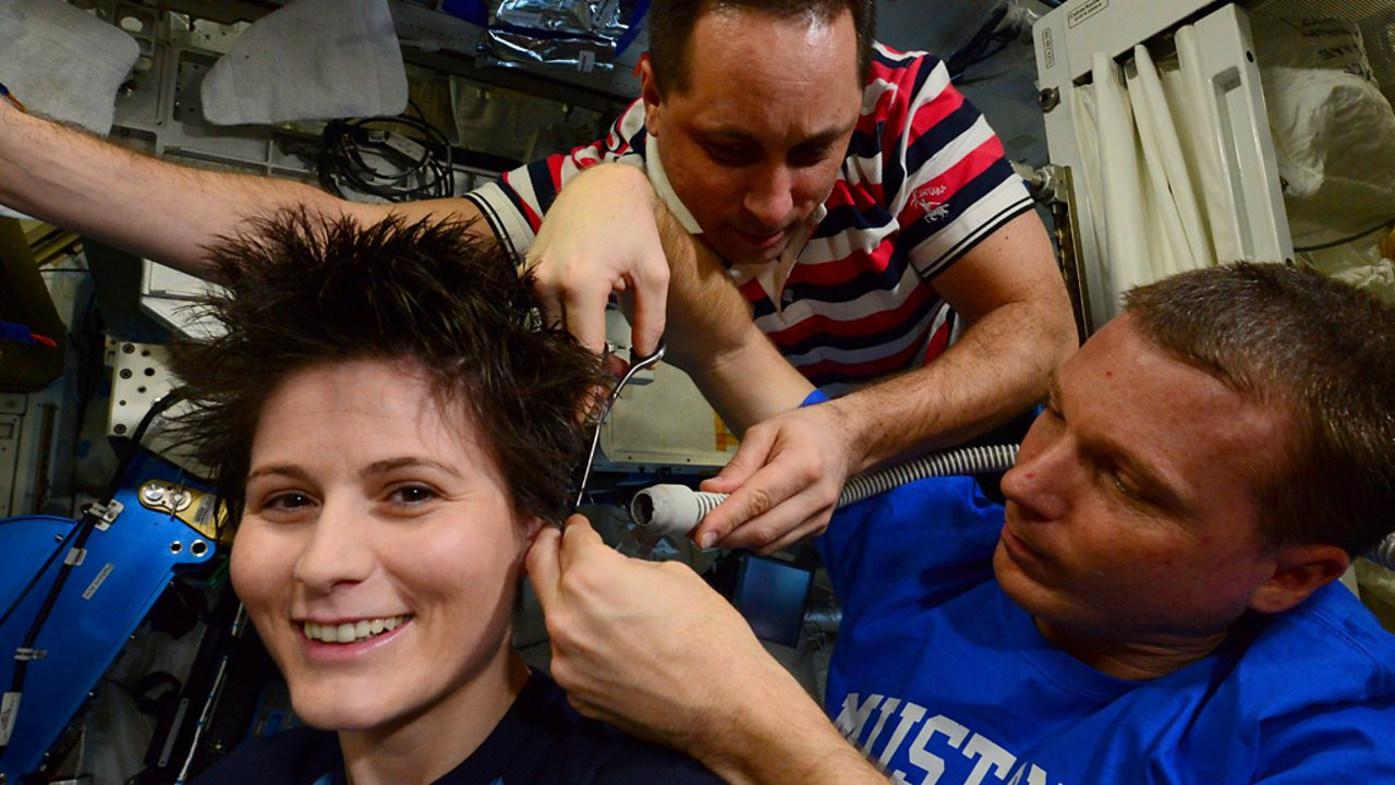 Crew members on the ISS give a fellow astronaut a haircut using scissors and a vacuum.
