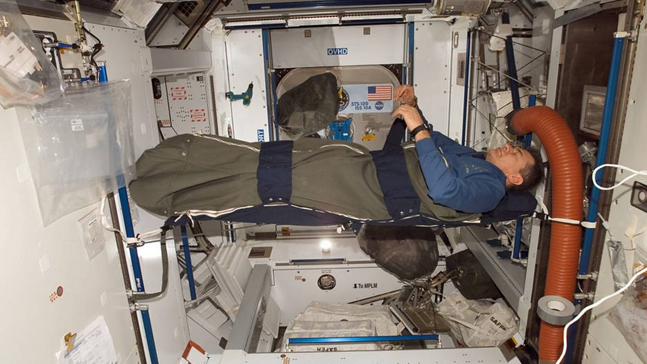 An astronaut sleeps suspended in a sleeping bag attached to the inner walls of the ISS.