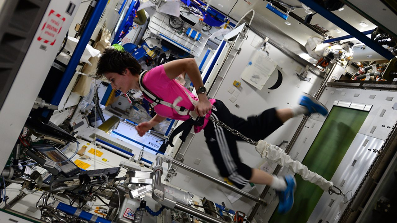An astronaut is weighted down to a treadmill by chains connected to her waist.