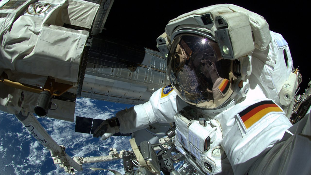 An astronaut outside the ISS with the backdrop of Earth surrounded by space.