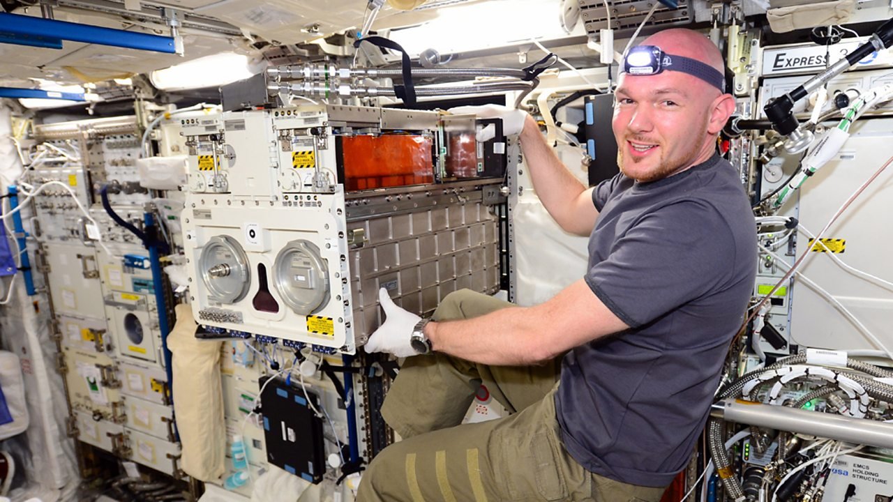 Astronaut Alexander Gerst moves laboratory equipment within the ISS.