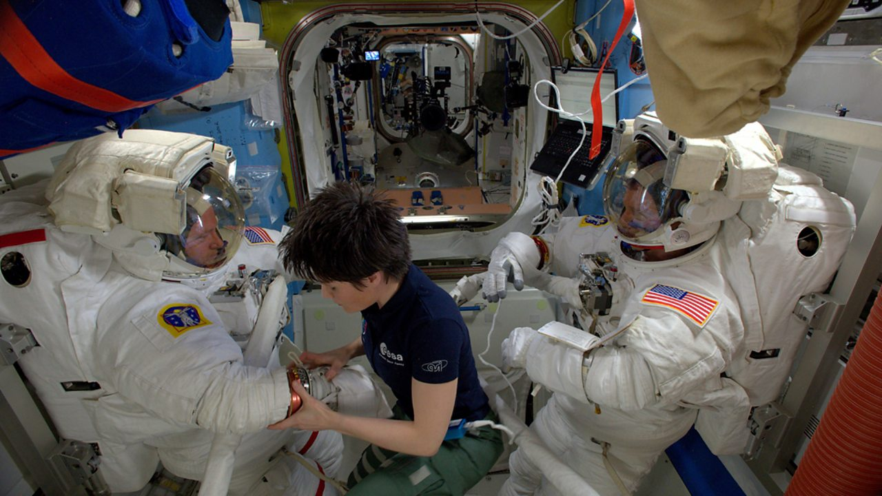 Astronaut Samantha Cristoforetti helps two fellow crew member dress for a spacewalk.