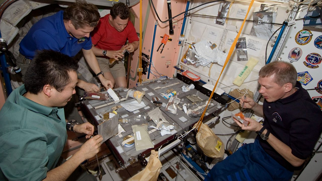 Twenty crewmembers share a meal on the International Space Station.