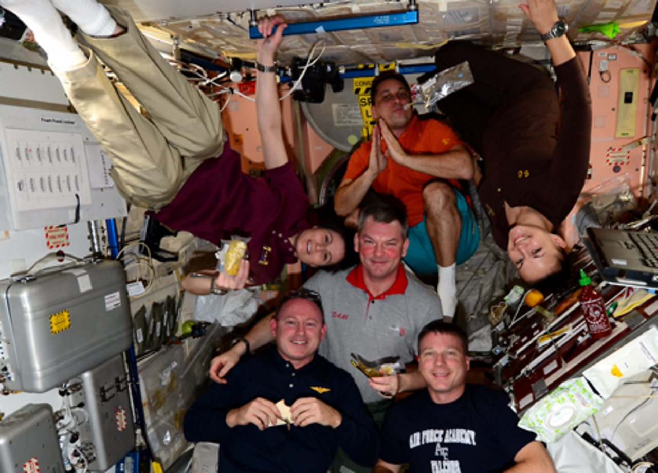 Six crewmembers float in the ISS, some upside down.