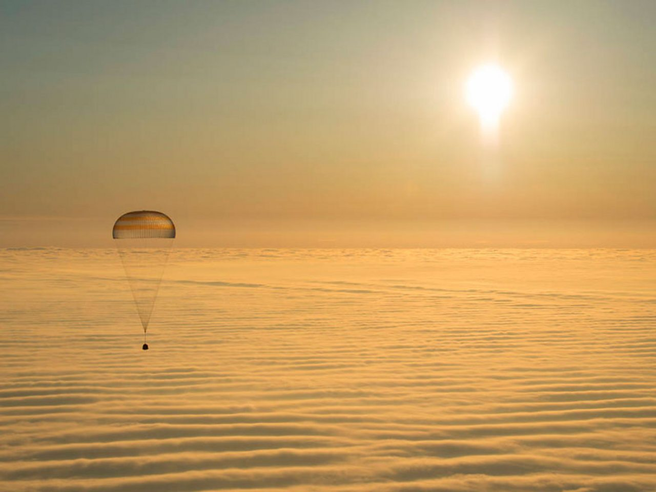 The Soyuz capsule hanging below a parachute returning to Earth.