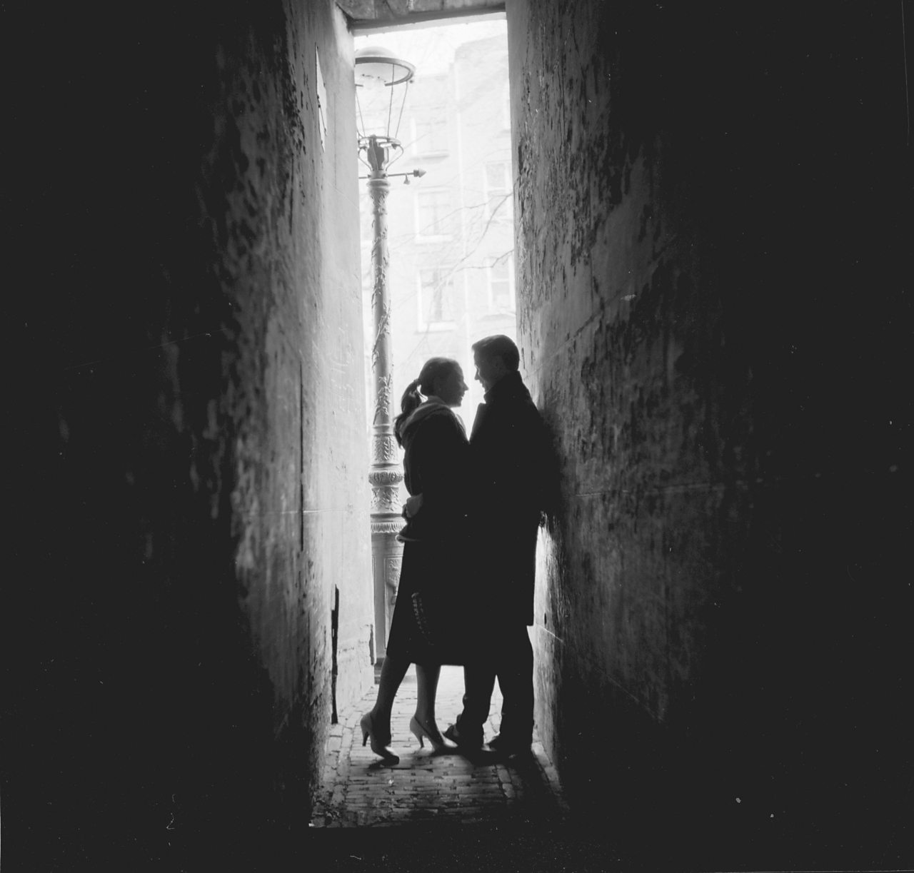 Photograph of a couple in an alley way, suggesting they are engaged in an extra-marital or illicit affair.