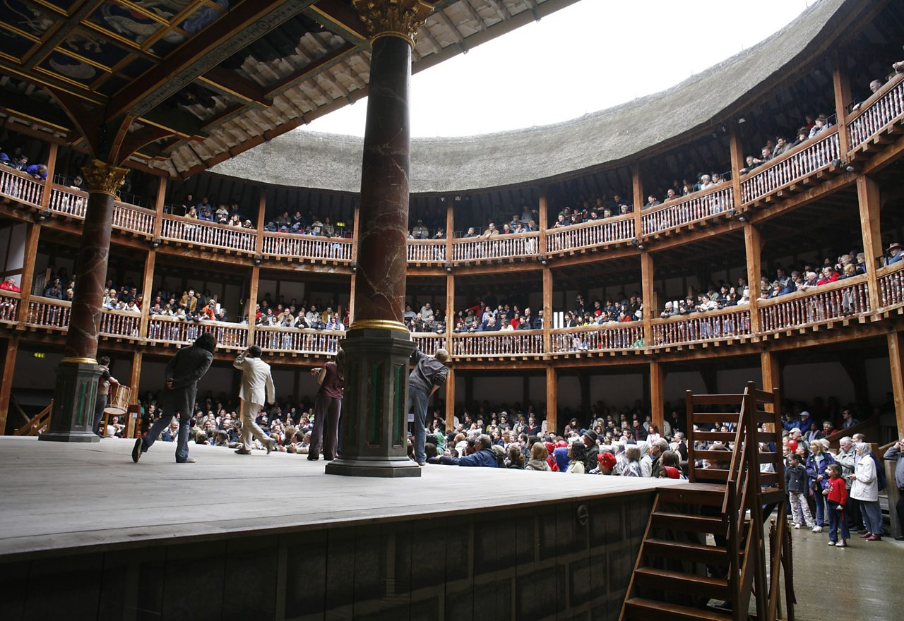 Inside Shakespeare's Globe theatre. Half of the audience are standing to watch the performances.