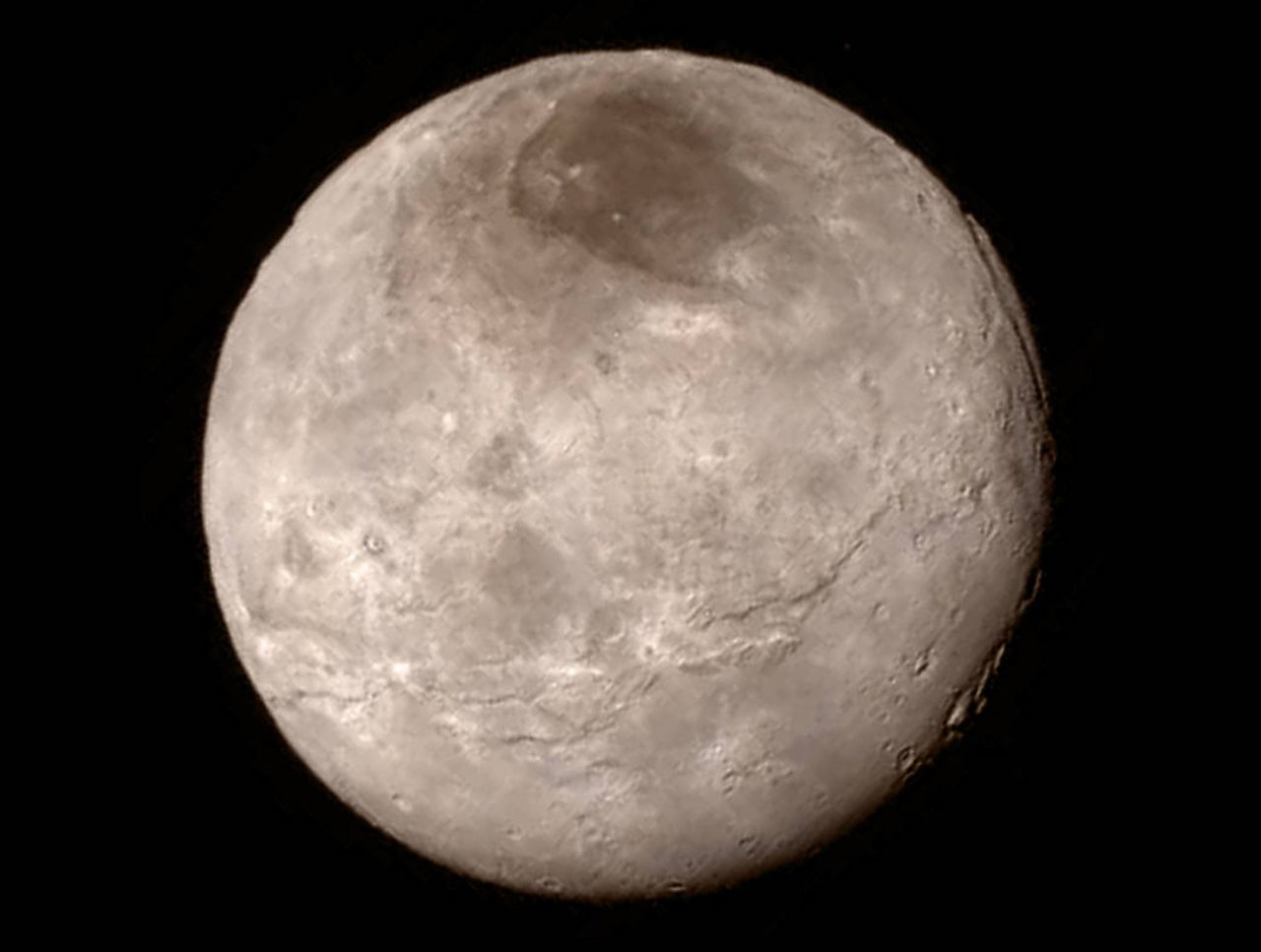 An image of Pluto with an enormous canyon that can be seen on the top-right of the image