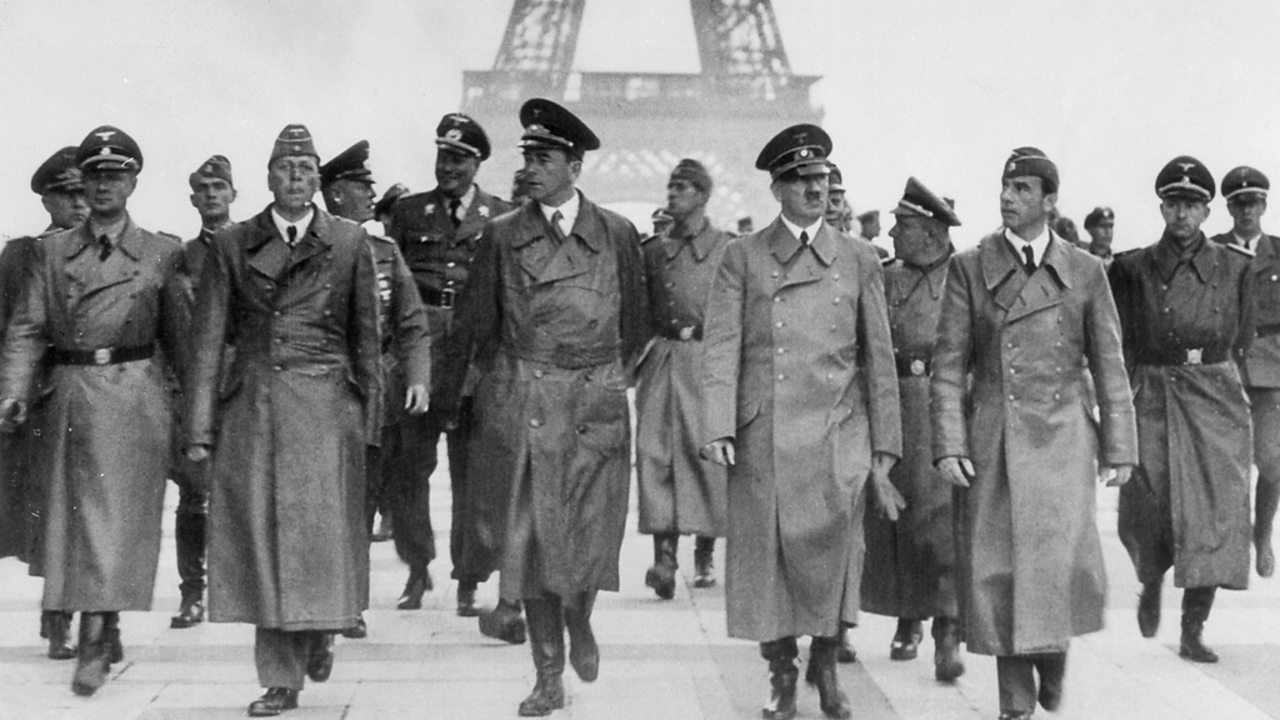 Hitler and other Nazi figures standing in front of the Eiffel Tower in Paris.