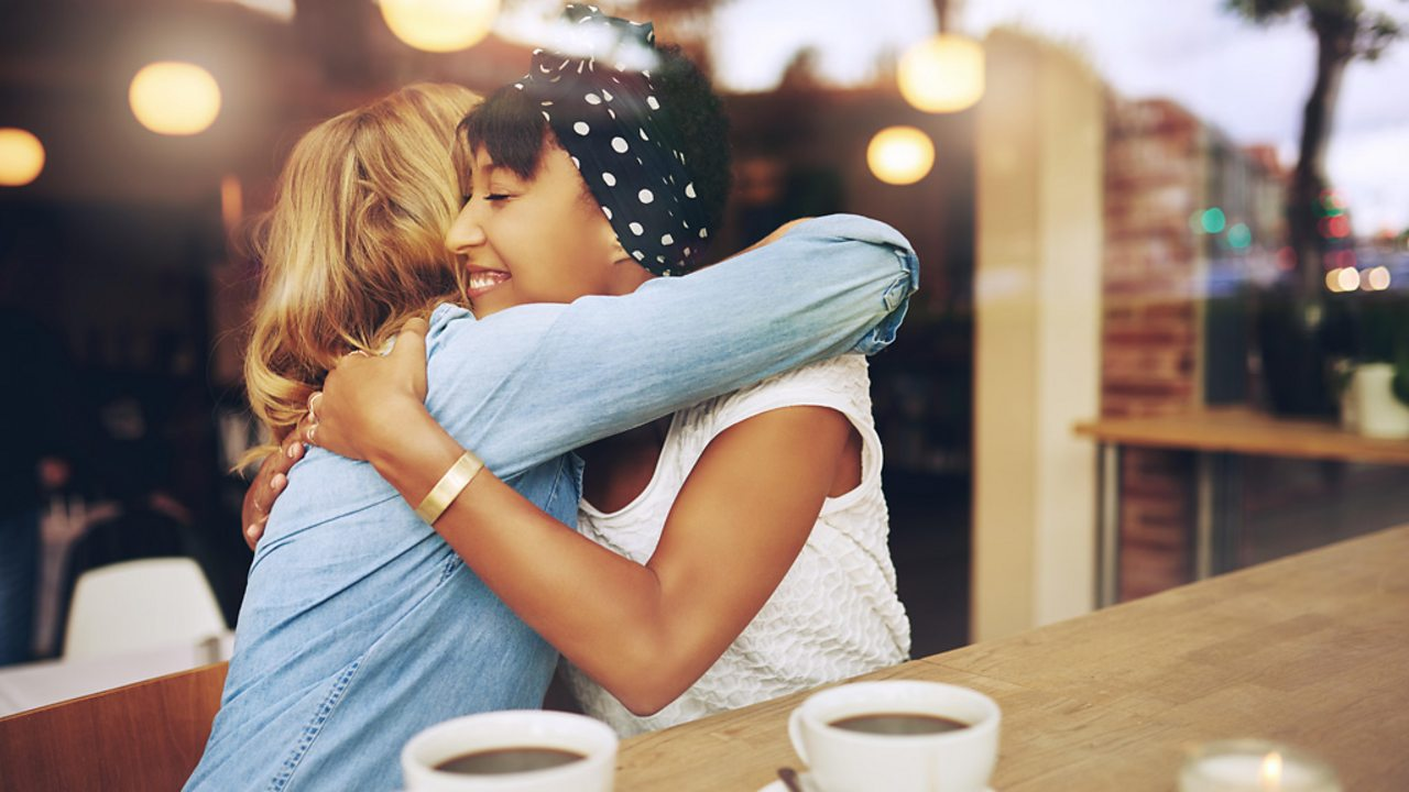 Two women hugging one another.