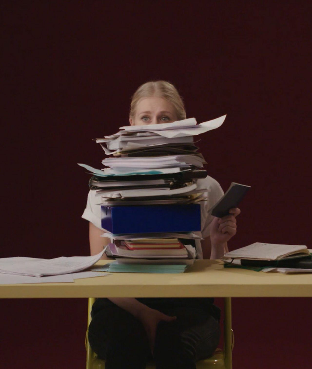 Files stacked with a girl peering over the top