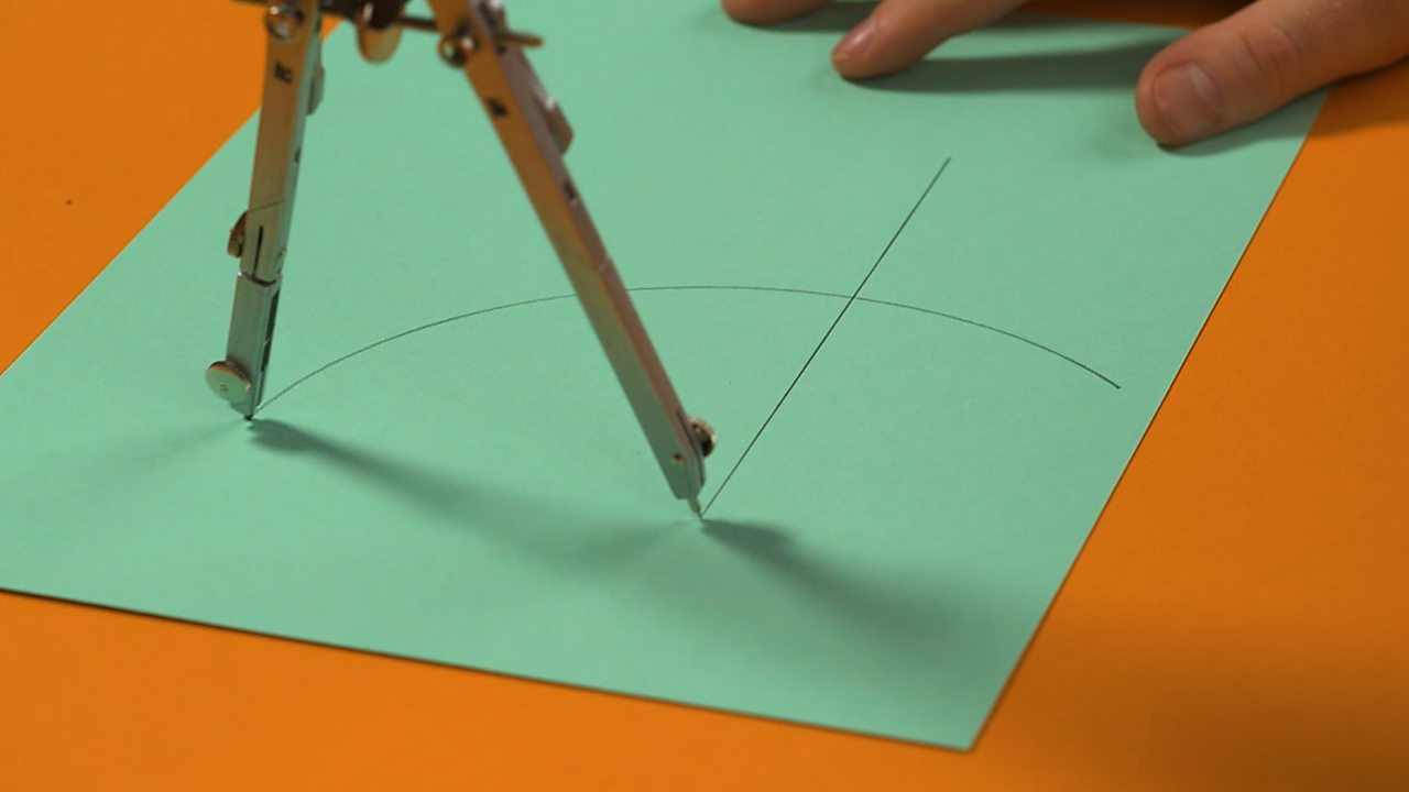 Someone drawing an arc through the line with a compass